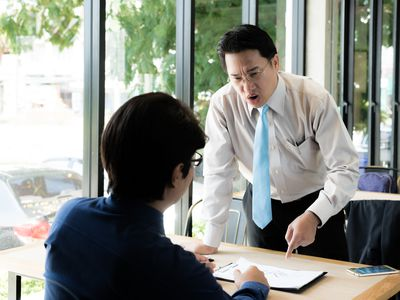 Asian manager of businessman complaining to employee by pointing to him for mistake work, stressed feeling in cafe office