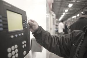 Worker scanning time clock with his id card