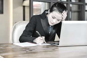 Business woman writing a candidate rejection letter.