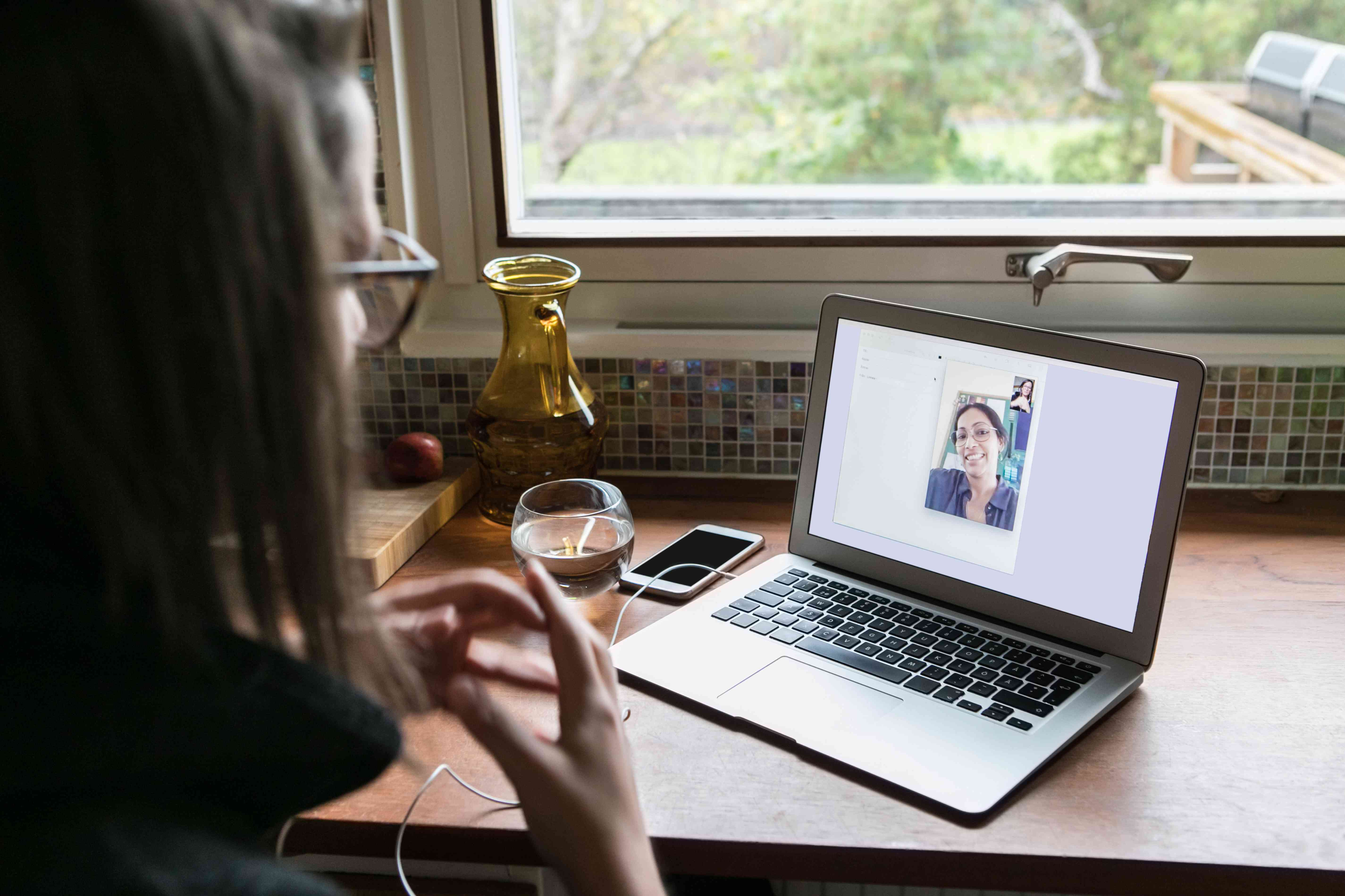 High angle view of businesswoman video calling female colleague on laptop in home office