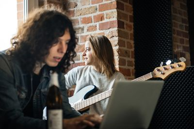 woman playing a guitar while a young man types on a laptop