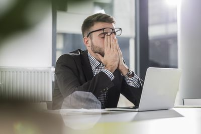 Exhausted young man with laptop in office