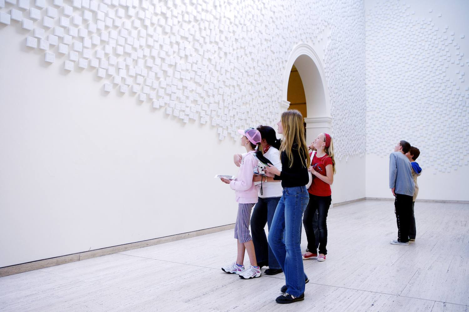School students in a art gallery marveling over a full wall display piece.