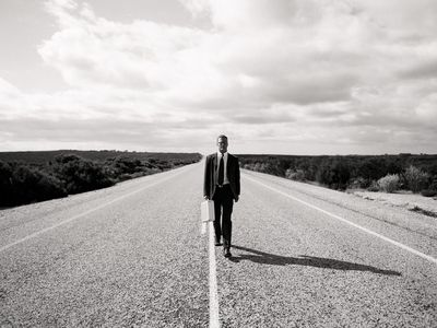 A person carrying a briefcase walking on a desert highway, symbolizing a mid-career crisis.