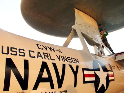 A U.S. Navy Aviation Electronics Technician completes a maintenance check on the radar dome of the E-2C 'Hawkeye'