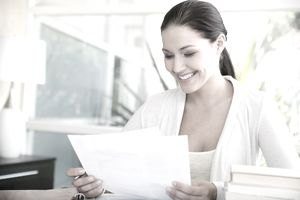 Woman looking over a thank you note from her executive employer.