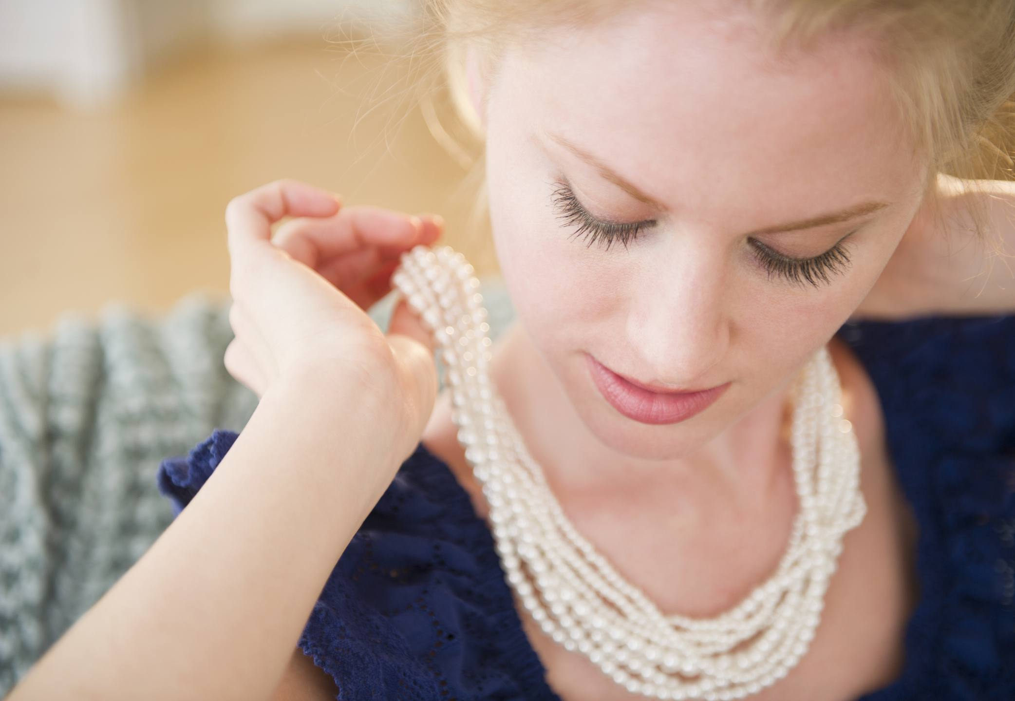 Woman fastening a layered pearl necklace