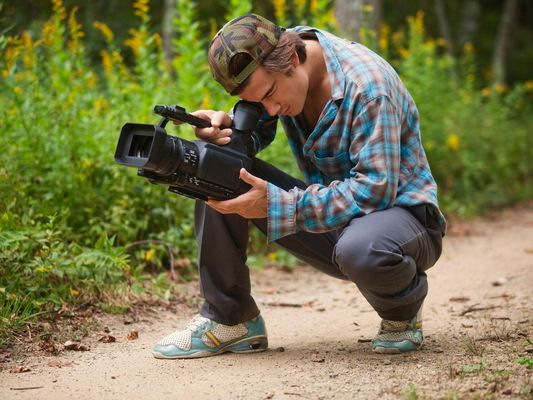 Young man shooting HD video on a trail