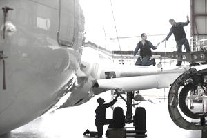 Engineers repairing wing and landing gear on passenger jet in hangar