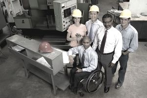 Workers in hard hats surrounding and supporting employee in a wheelchair