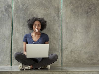 African American college student using laptop and blowing bubble gum bubble