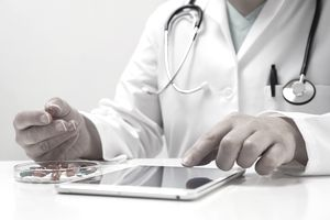 a pharmacist holds a pill in one hand and works on a tablet with the other