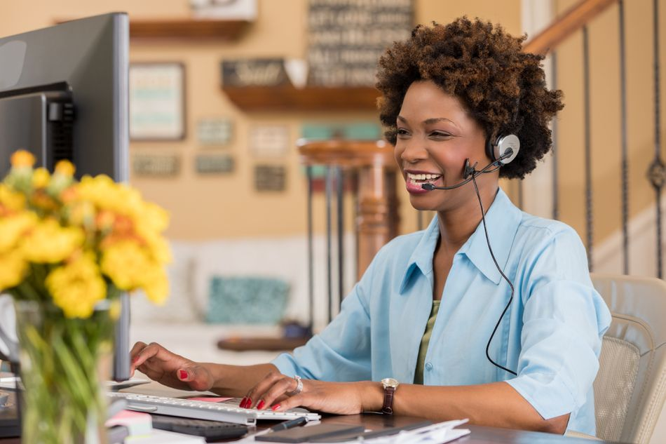 Cheerful African American woman uses headset while talking with client
