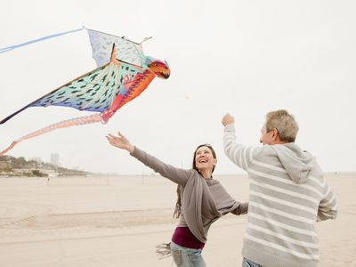 Middle agedman and woman fly a colorful kite on a beach