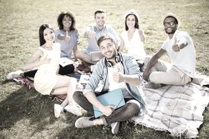 Six young professionals sitting on a blanket in the park