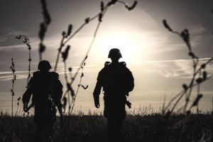 Silhouette Army Soldiers Standing On Field During Sunset