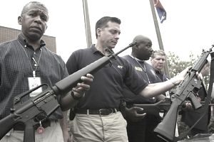 ATF special agents holding up rifles they confiscated during a raid.