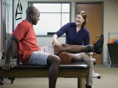 Female physical therapist assisting man with leg exercise