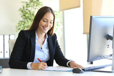 Woman signing business letter in office