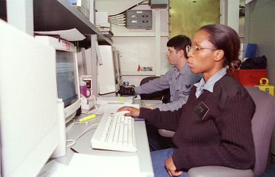 Two navy intelligence specialists working on computers on board an aircraft carrier.