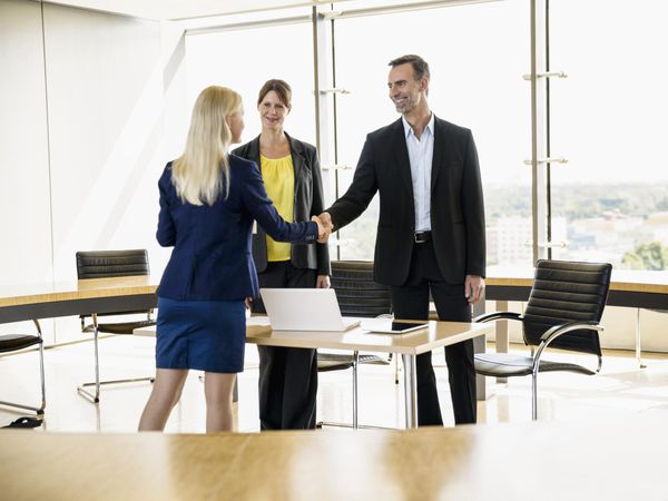 Business people in room smiling