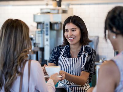 Female barista wearing apron smiling while handling a large mug of coffee to a customer.