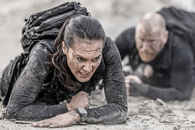 Redhead male and brunette female military swat security anti terror duo crawling together during operations in muddy sand