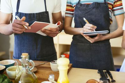 Close-up of man and woman taking notes in a cooking workshop