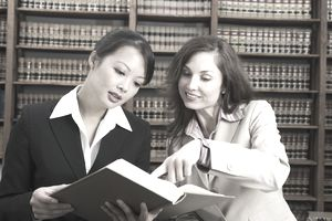 lawyer and paralegal in law library reviewing case law