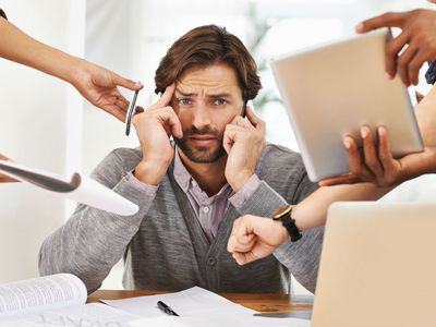 Stressed manager with a lot of people looking for his help