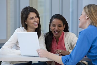 one woman talking to two fellow female co-workers