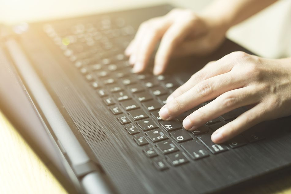 Close-up photograph of a woman's hands working with her laptop