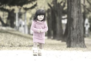 female child model in pink sweater dress and boots in park in autumn