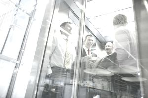 Businessmen talking in elevator