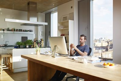 Man sitting at computer in kitchen of his apartment