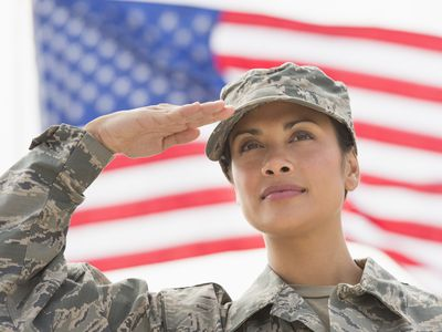 Female army soldier saluting, American flag in background