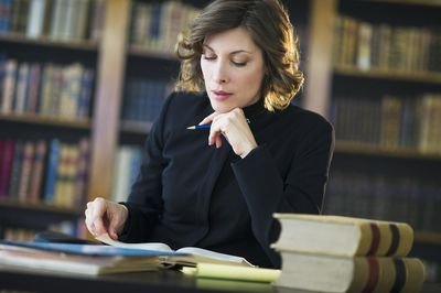 Legal professional studying at a library table with books
