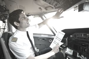 Male pilot checking control panel in airplane cockpit