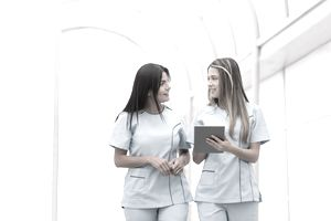 Two nurses talking at the hospital as they walk down a corridor.