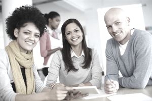 Three diverse, attractive employees in a business casual meeting