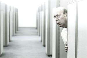 older man peering around a cubicle representing the concept of being watched at work.