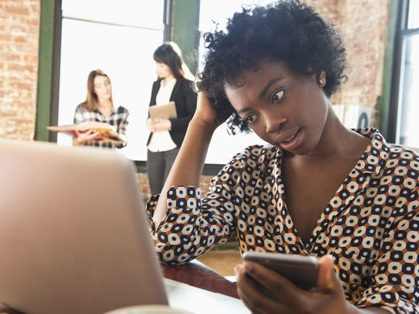 Confusing businesswoman using cell phone and laptop in office