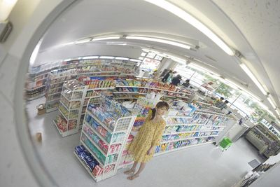 Young woman in mirror at store