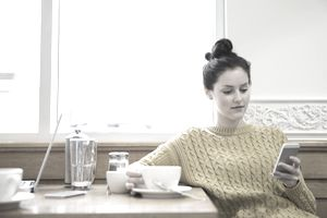 Woman in cafe using smart phone