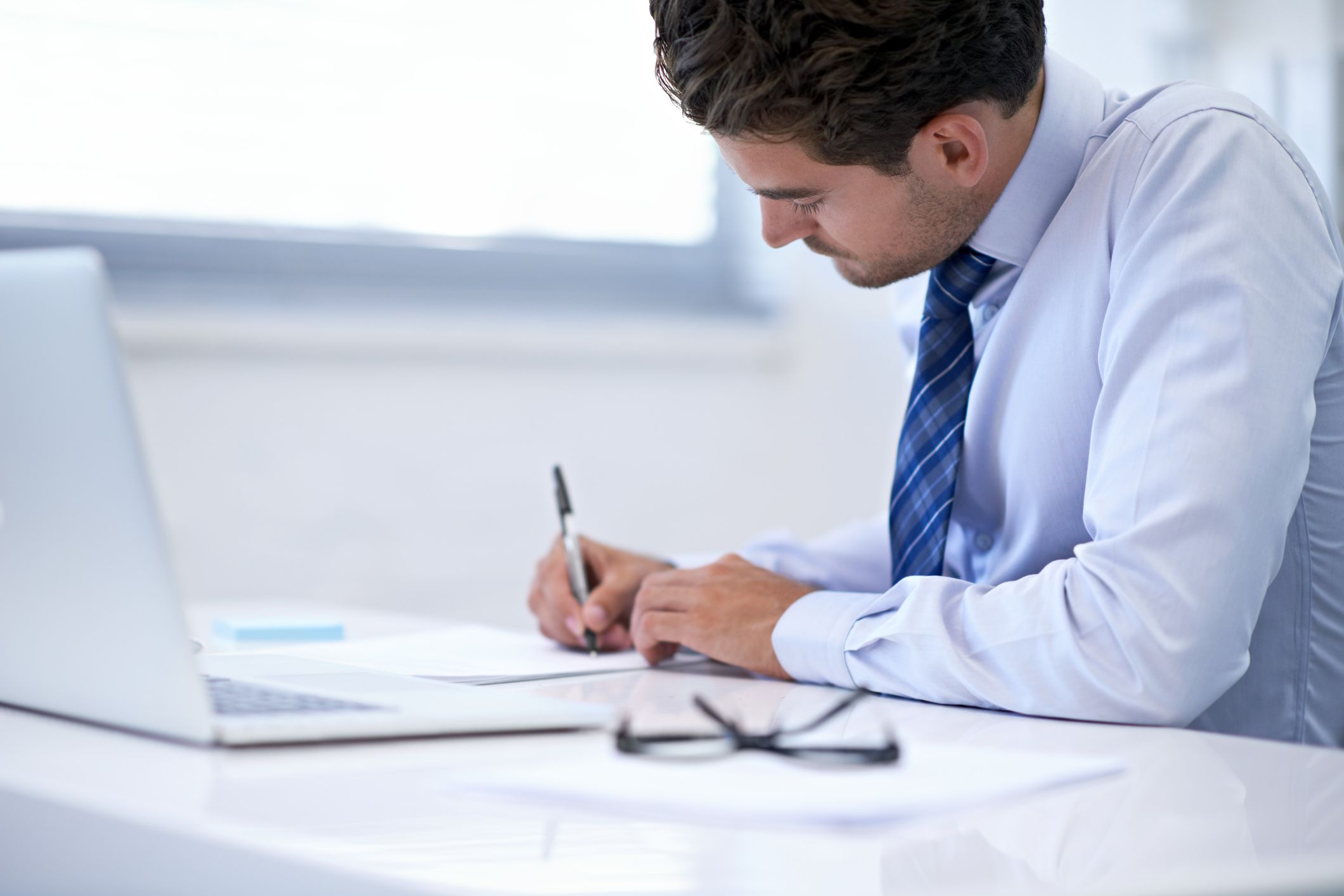 A man signing a letter of resignation.