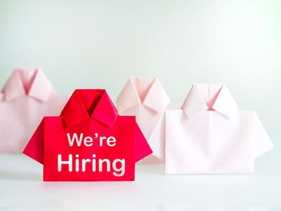 One Red among white origami shirt paper with We're Hiring message text , recruitment Human resource for the employee unique individuality and difference or leadership concept.