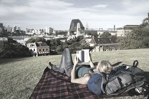 Backpacker reading her guidebook in Observatory Park, overlooking Sydney harbour.