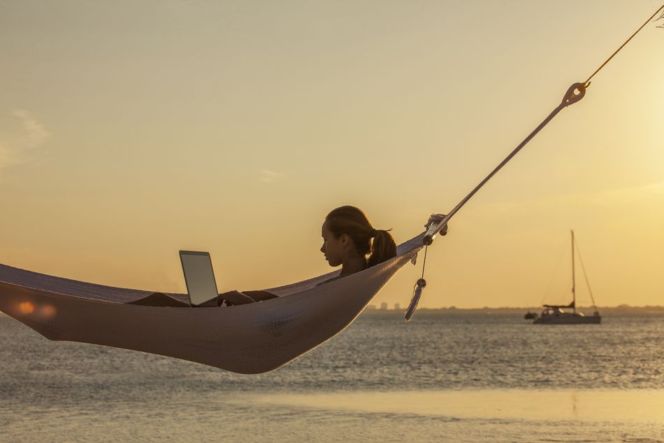 Caucasian woman using laptop in hammock