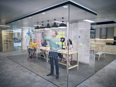 Work colleagues brainstorming in glass office