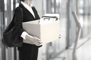Businessperson leaving office with box of personal items after being terminated for cause.